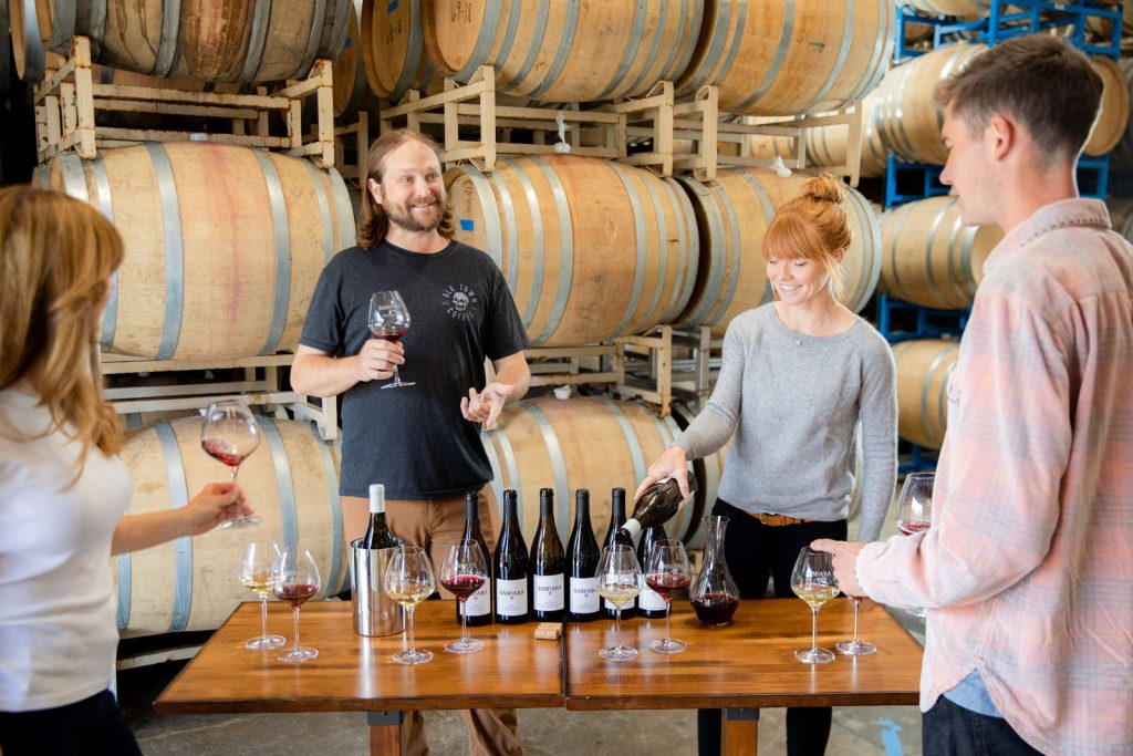 Winemaker Matt Brady leading a tasting in front of barrels